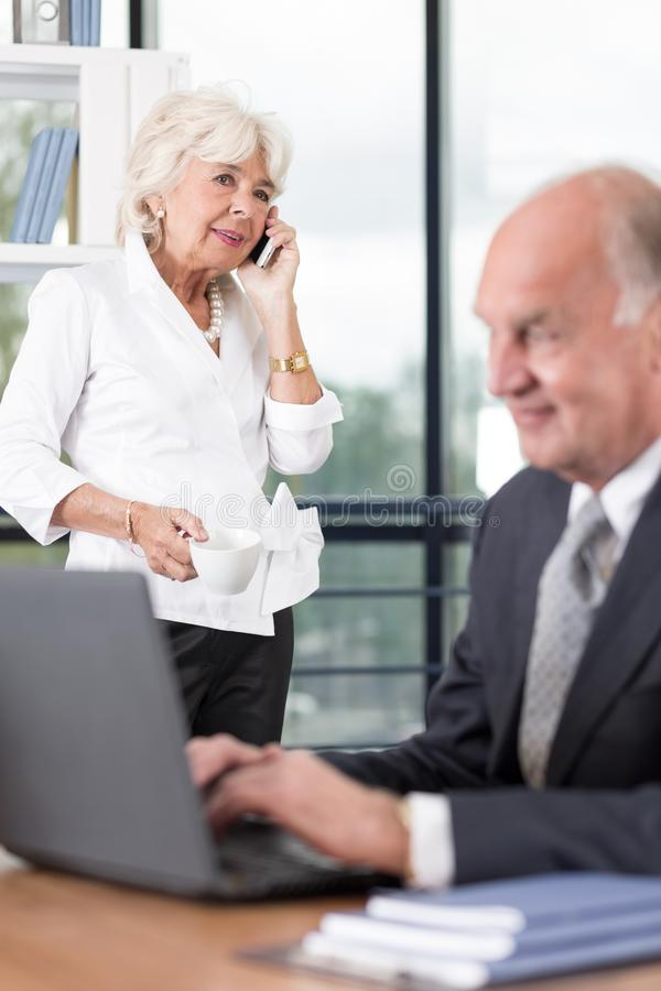 Senior business couple working. With laptop and phone stock images