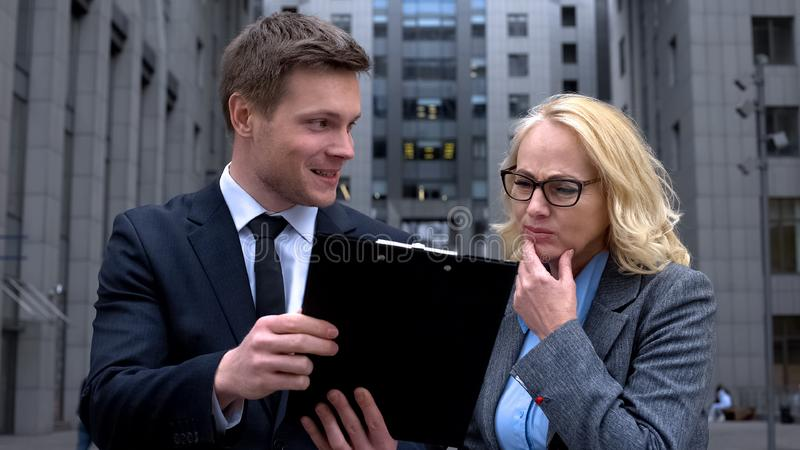 Senior business lady criticizing business project offered young male colleague stock photography