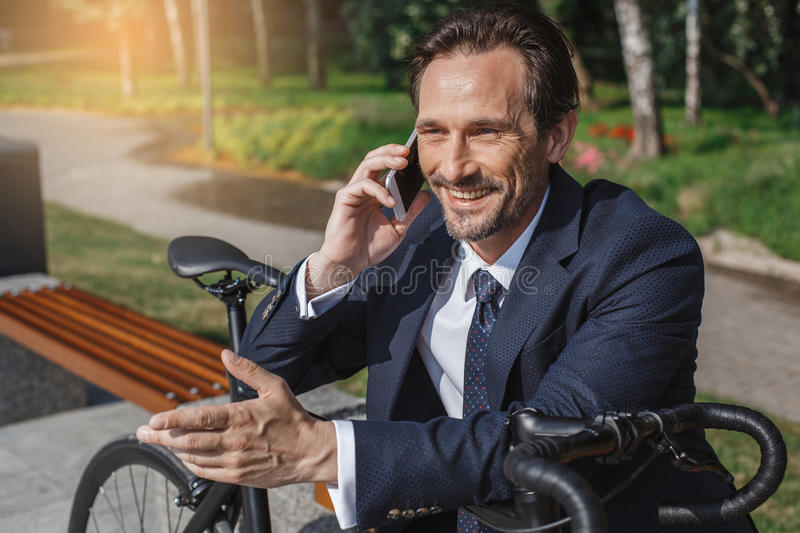Senior business man with a bicycle outdoors stock photo