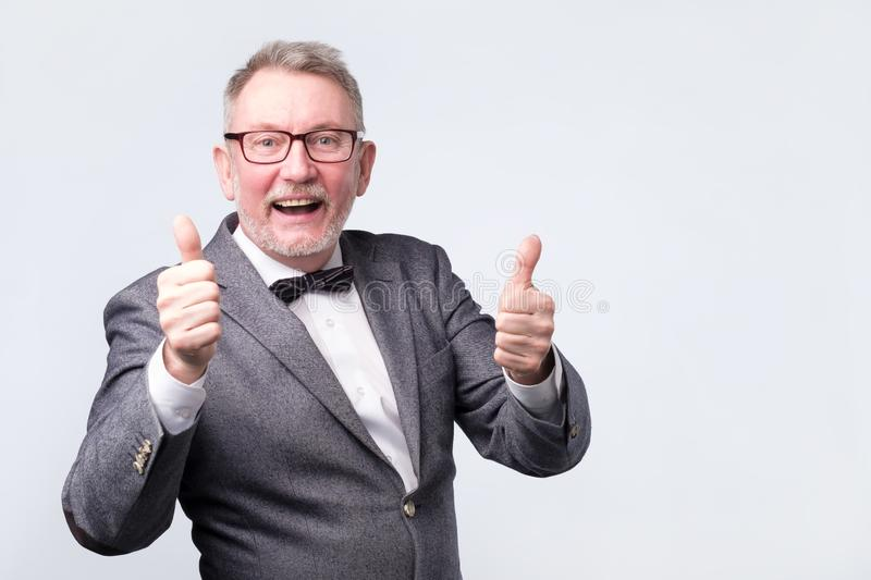 Senior business man with bow tie showing thumbs up royalty free stock images