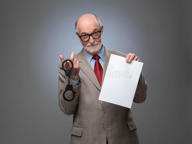 Business man with handcuffs and contract stock photos