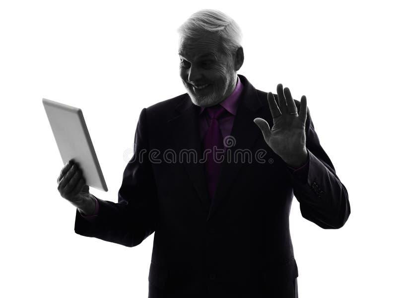 Senior business man holding digital tablet saluting silhouette stock photos