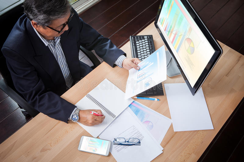 Senior business man looking to business paper graph report in ha royalty free stock photography
