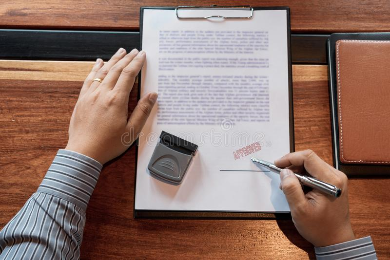 Senior business man male hand putting or signing signature in the certificate contract after approve stamp on loan document stock image