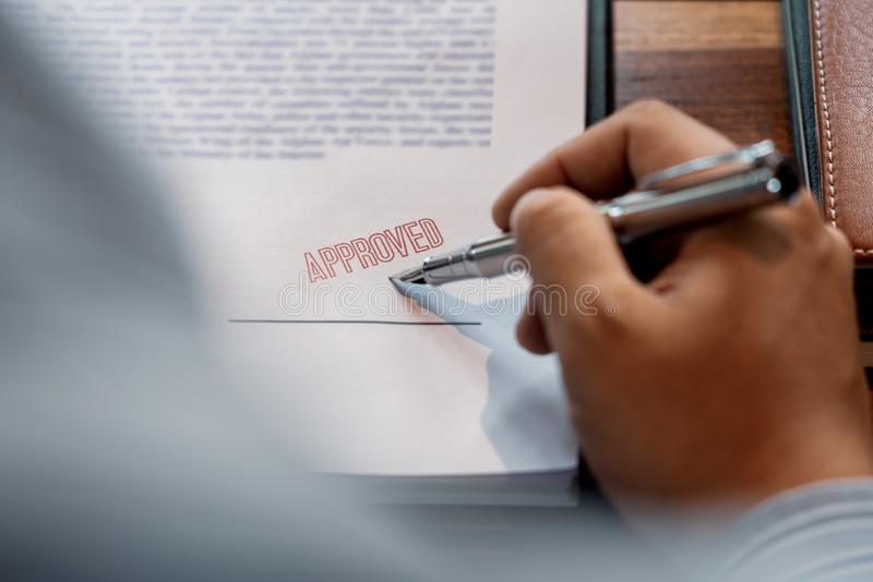 Senior business man male hand putting or signing signature in the certificate contract after approve stamp on loan document royalty free stock images