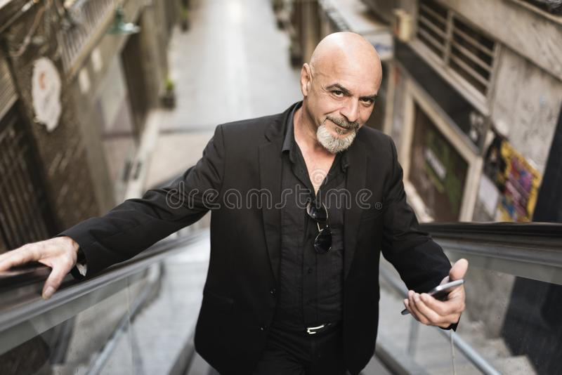 Senior business man in scalator with smartphone royalty free stock photo