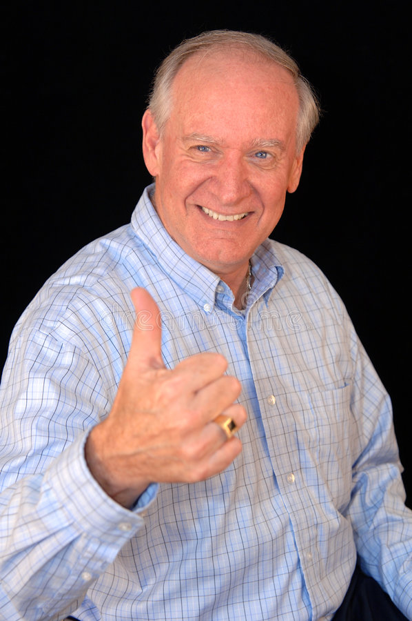 Senior business man thumbs up. An older smiling business man in a blue shirt with thumbs up against a black background (focus on face stock image