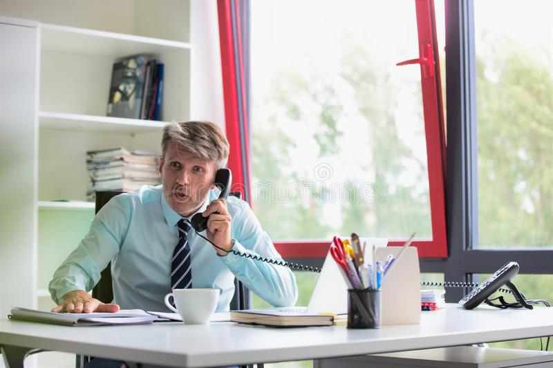 Senior business man working whilst making telephone call, he looks shocked and slamming his hand on his desk royalty free stock images
