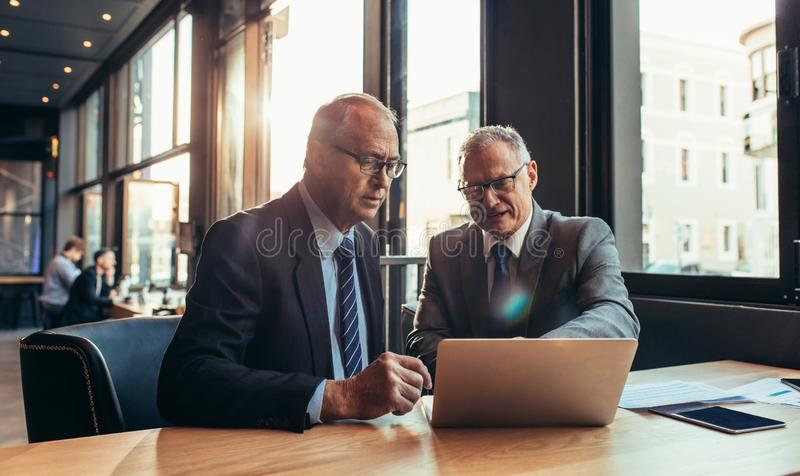 Senior business partners discussing a project at the cafe stock photo