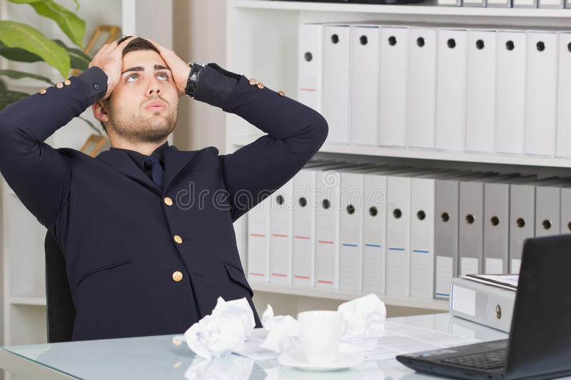 Senior business person sitting at office desk looking up and be. Ing frustrated from too much work stock photos