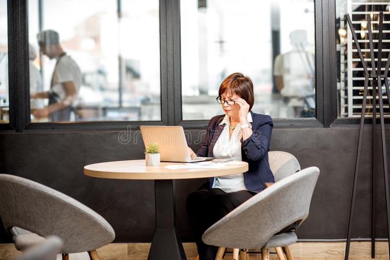 Business woman working in the cafe. Senior business woman dressed in the suit working with laptop in the modern cafe royalty free stock images