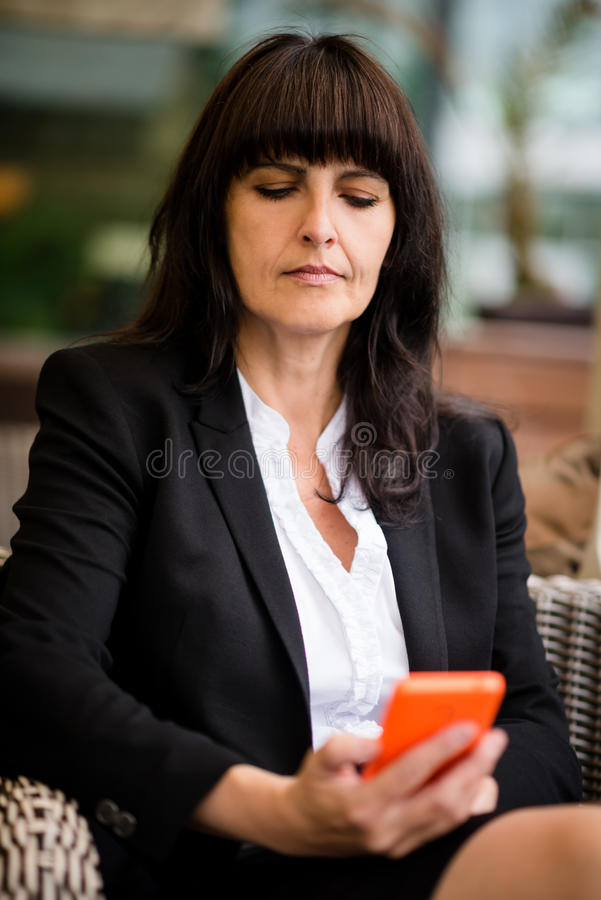 Senior business woman with phone. Senior business woman sitting in chair and looking to her phone stock photography