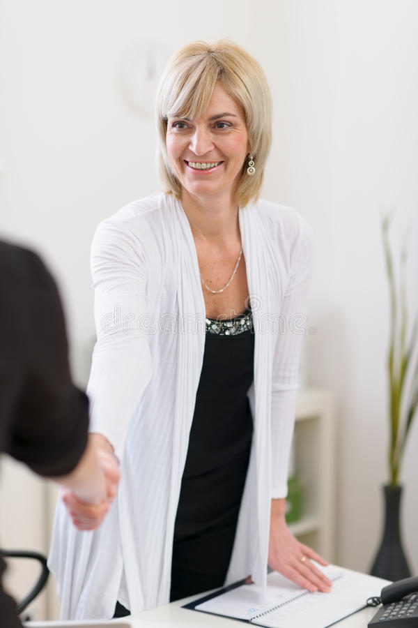 Senior business woman shaking visitors hand stock images