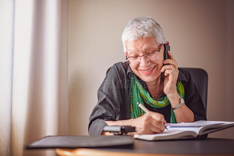 Senior business woman taking down orders stock photography