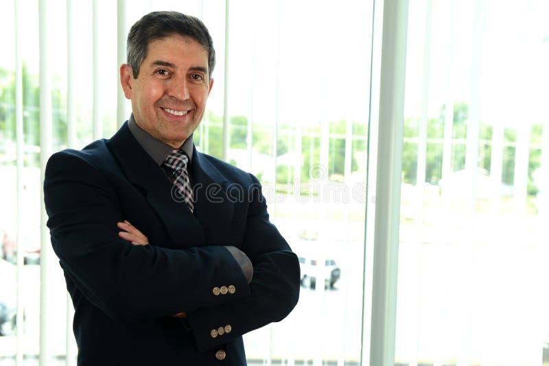 Senior Businessman. Senior hispanic businessman smiling with his arms crossed inside an office building stock photos