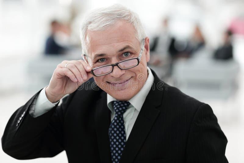 Closeup of a senior businessman adjusting his glasses royalty free stock images