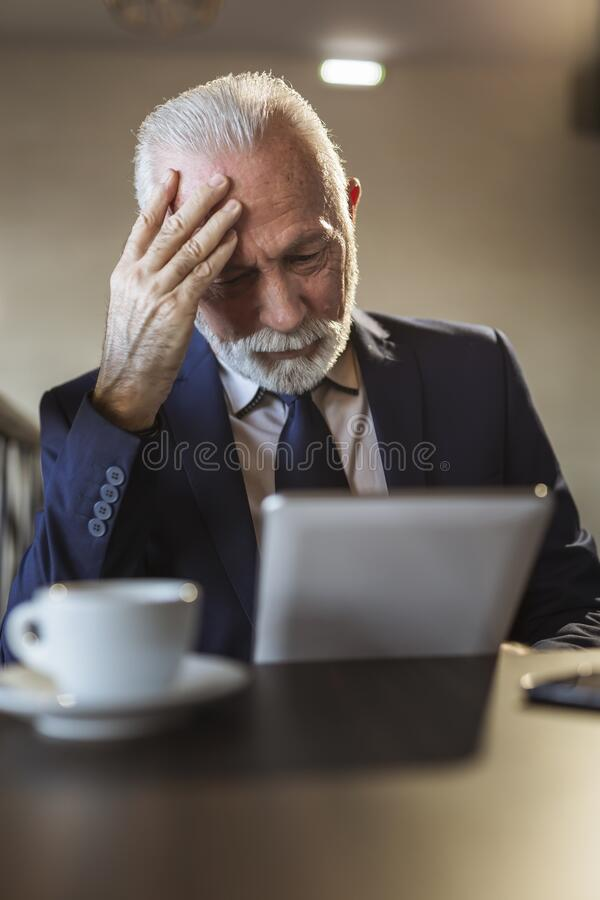 Senior businessman analysing statistics on tablet computer. Senior businessman in a restaurant, analysing business success statistics using a tablet computer royalty free stock photo