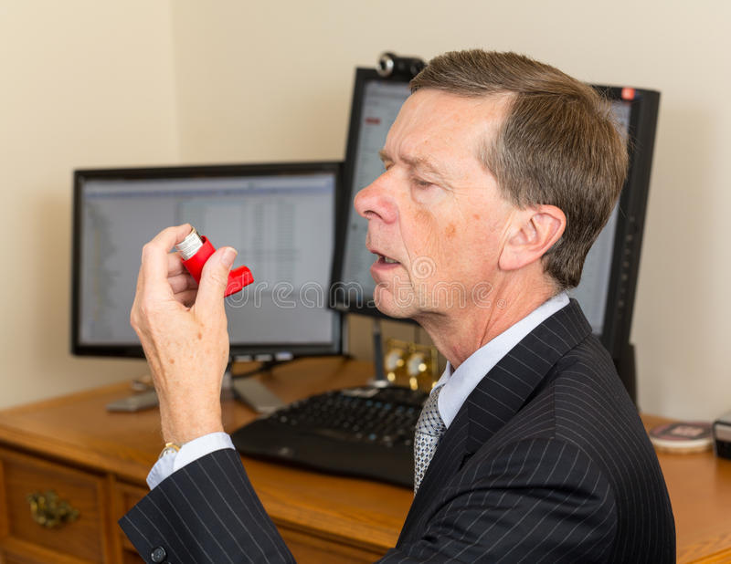 Senior businessman with asthma inhaler. Senior caucasian man in suit at desk with computer screens with asthma inhaler to handle problems with breathing royalty free stock photos