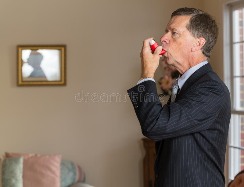 Senior businessman with asthma inhaler. Senior caucasian man in suit at home with asthma inhaler to handle problems with breathing stock photos