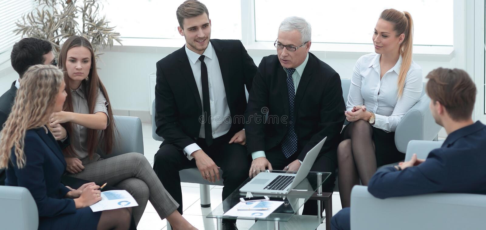 Senior businessman and business team sitting in the lobby of the modern office. royalty free stock image