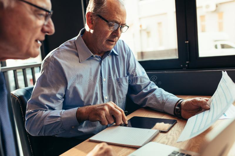 Senior businessman with colleague analysing a report at cafe royalty free stock photo