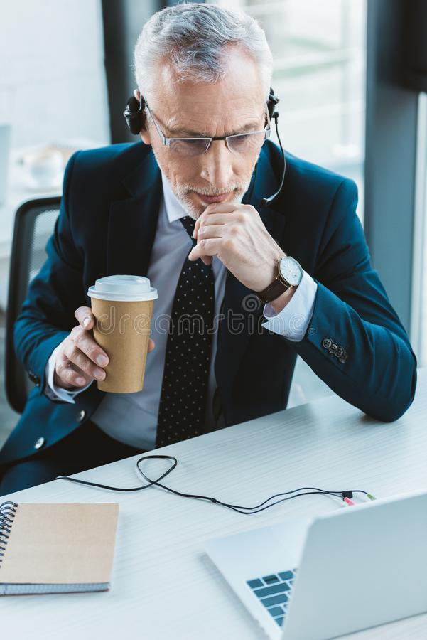 Senior businessman in eyeglasses and headset using laptop and holding. Paper cup stock images