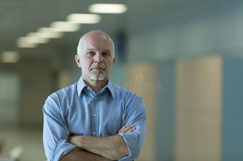 Senior businessman with folded arms indoors. Half body portrait of senior businessman with folded arms and thoughtful expression royalty free stock image