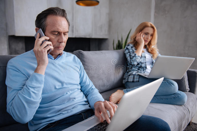 Senior businessman freelancing with wife at home. Without time for private life . Confident charismatic aged men sitting at home and using modern devices with stock images
