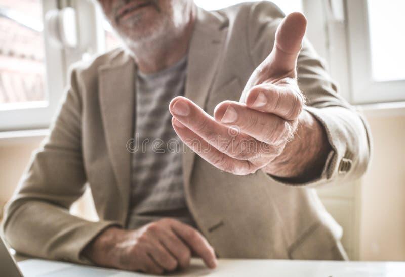 Senior businessman giving helping hand. Focus on hand. royalty free stock photos