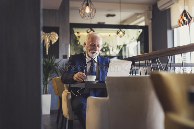 Senior businessman having a conference call in a restaurant. Senior businessman sitting at a restaurant table, drinking coffee and having a conference call on a royalty free stock photography