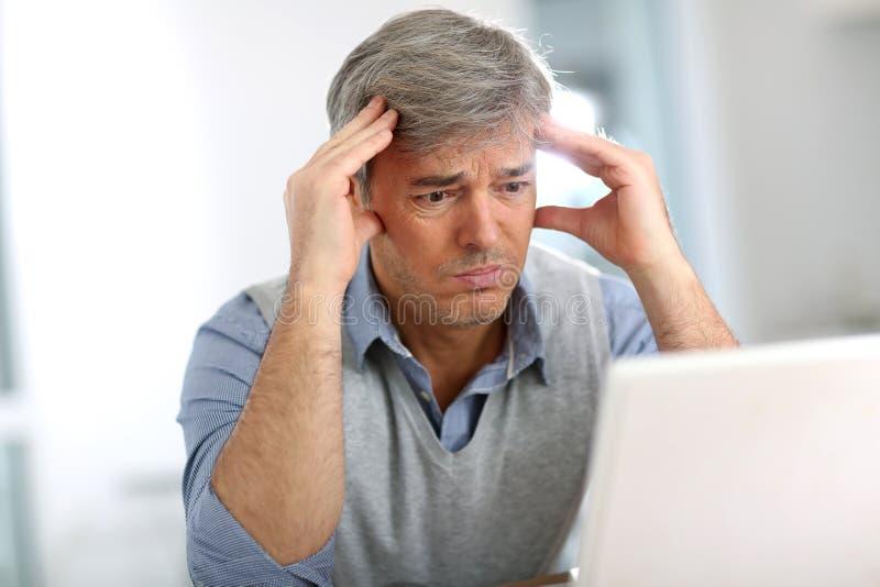 Senior businessman having a headache. Senior businessman in front of laptop having a headache royalty free stock photos