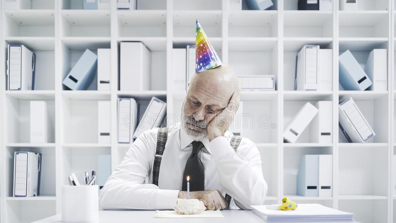 Senior businessman having a sad lonely birthday royalty free stock image
