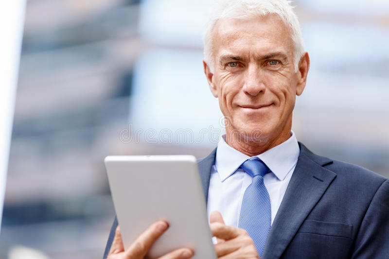 Senior businessman holding touchpad. Outdoors royalty free stock photos