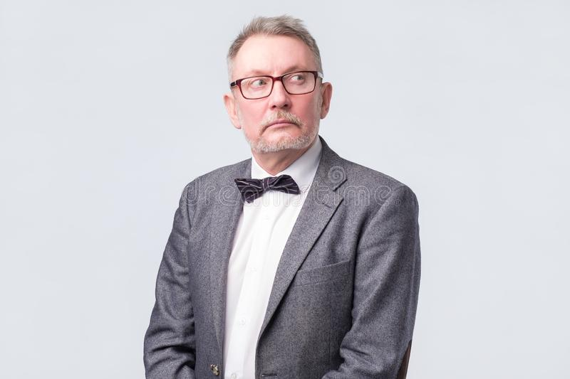 Senior businessman in jacket, glasses and tie looking up aside stock photography