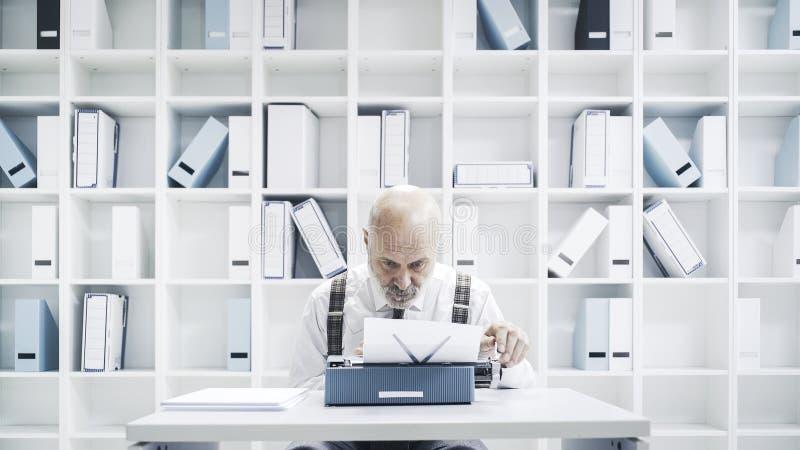 Senior businessman working with a typewriter stock photo