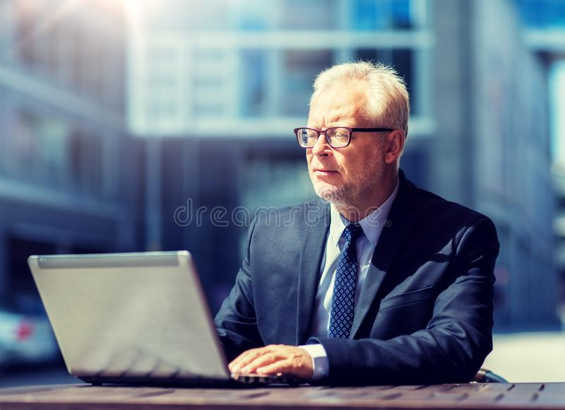 Senior businessman with laptop at city street cafe royalty free stock image