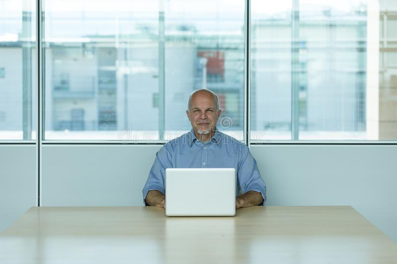 Senior businessman with laptop in office royalty free stock photography