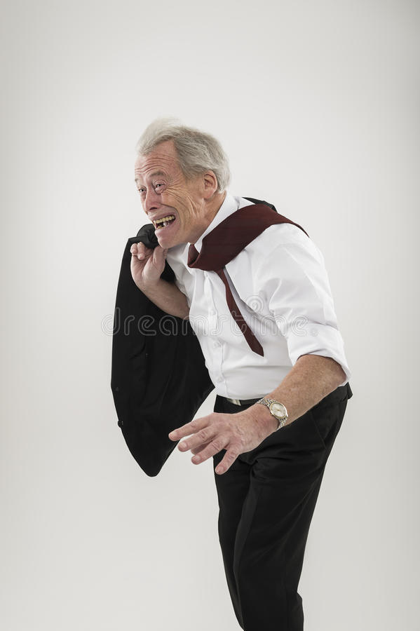 Senior businessman leaning forwards into wind. In a stooped stance like an aged man with his tie flapping over his shoulder as he battles the elements royalty free stock photos