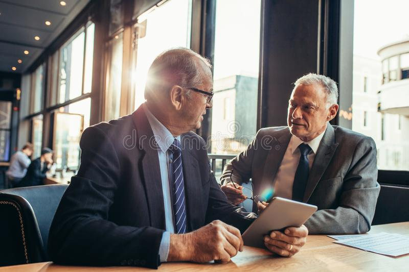 Senior businessman listening to his partner at the cafe royalty free stock image