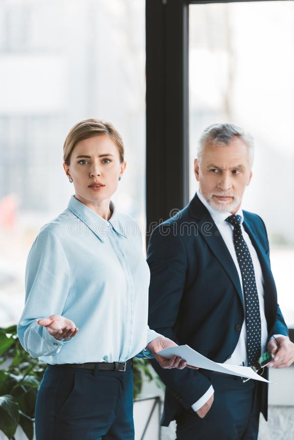 Senior businessman looking at businesswoman holding papers and looking. At camera stock image
