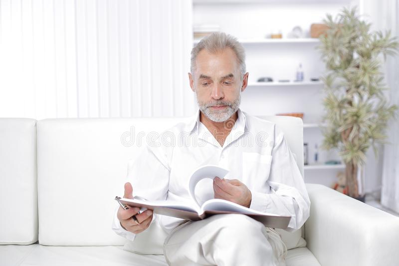 Senior businessman making a note in the workbook.  stock photography