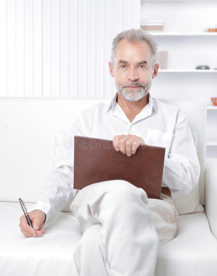 Senior businessman making a note in the workbook.  stock image