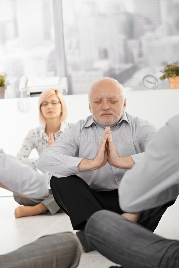 Senior businessman meditating in office stock photos