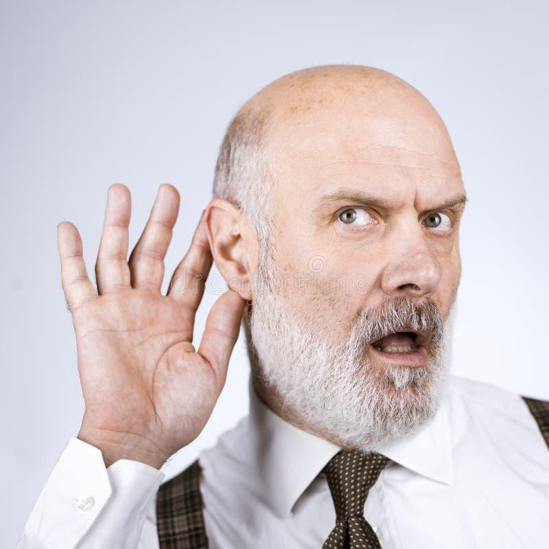 Senior businessman overhearing something stock photo