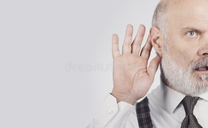 Senior businessman overhearing something stock images