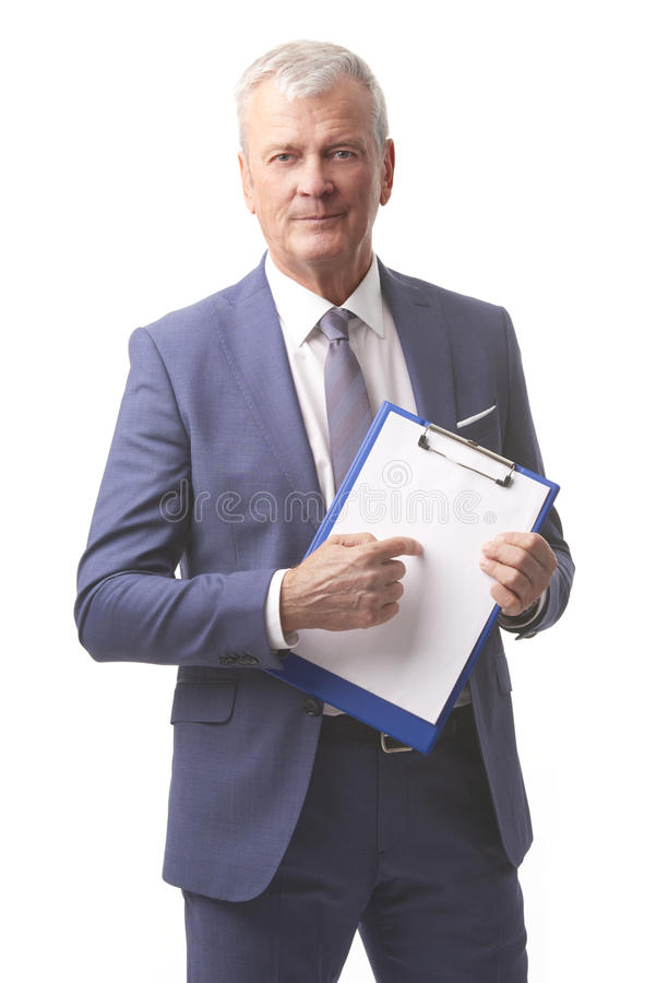 Senior businessman portrait. Shot of a senior account manager holding clipboard with blank paper and pointing up with his finger while standing at isolated white stock photography