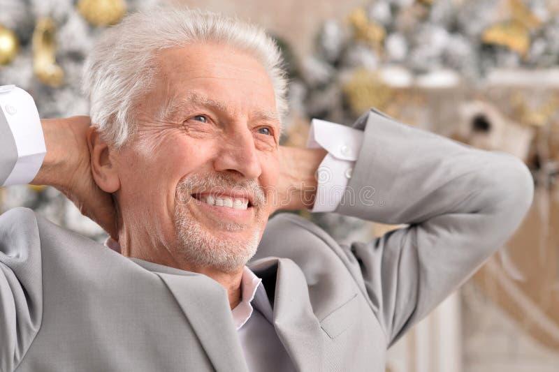 Senior businessman posing on blurred Christmas tree background royalty free stock photo