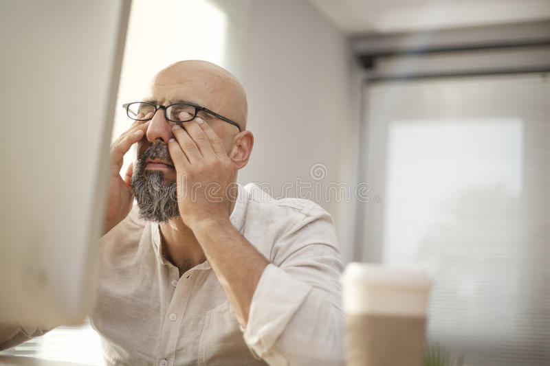 Senior businessman rubbing his tired eyes royalty free stock image