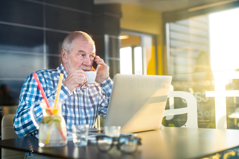 Senior businessman with smartphone and laptop in cafe stock photo