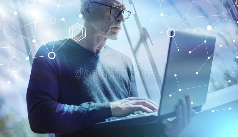 Senior businessman standing and working on his laptop; multiple exposure. Senior businessman standing and working on his laptop in office; multiple exposure stock photography